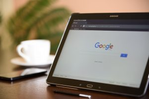 A tablet sitting on a desk with an image of google on the home screen